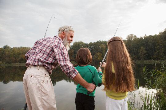 Rear view shot of a senior fisherman teaching his grandkids fishing on the lake