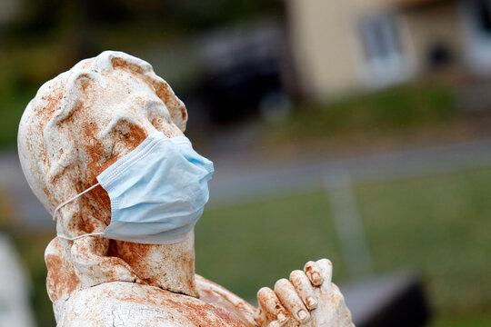 Statue dans un cimetière avec un masque facial jetable pendant la pandémie de Covid-19