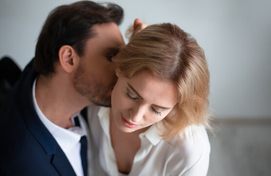 Business man kissing neck of young blonde woman closed eyes. Passion kiss. Enjoyment or workplace romance concept.