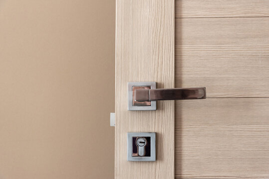 Close up stylish modern open wooden door with shiny silver and golden metal knob and lock near beige color wall extreme close view. Details of contemporary design