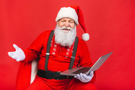 Close up photo of funny funky overweight santa claus using laptop search christmas season discounts type congratulations isolated over red background.