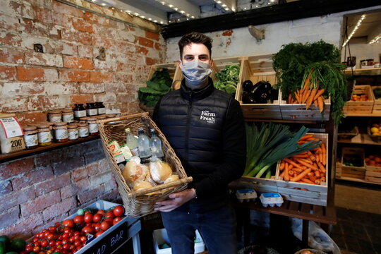 Alex Stephens, the owner The Farm Fresh Market, wears a face mask as he poses for a picture at his farm shop that has offered free lunches to children who need it over half term, as the spread of coronavirus diseases (COVID-19) continues, in Watnall