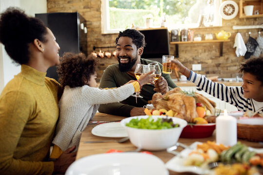 Happy black family toasting during Thanksgiving lunch at dining table.