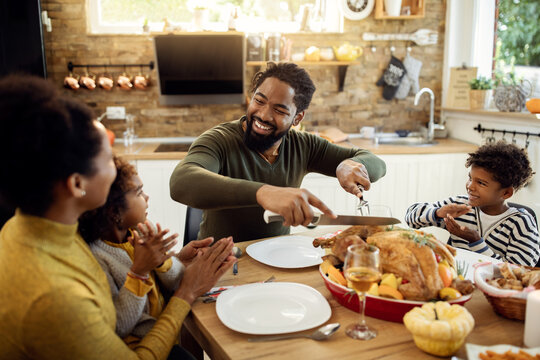 Happy black father carving roasted turkey during Thanksgiving lunch at dining table.