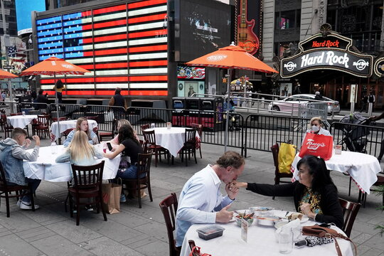 A man kisses a woman's hand after saying grace before dining outside at a pop up restaurant in New York