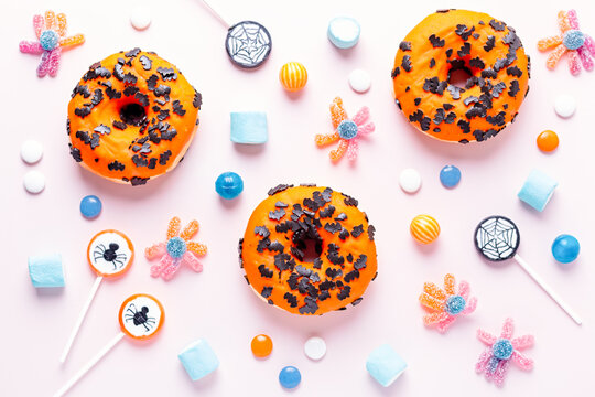 Pumpkin and chocolate donuts, spider lollipops, gummy candy and marshmallows on pink - Halloween candy flat lay on pink table, top view, kids party concept