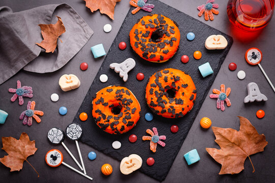 Pumpkin and chocolate donuts, spider lollipops, gummy candy and marshmallows on grey stone - Halloween candy flat lay on gray stone table, top view, kids party concept