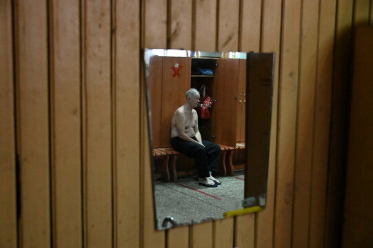 A man is reflected in a mirror as he visits a public banya in Omsk