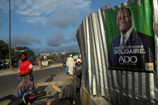 A woman walks past a campaign poster of a presidential candidate Alassane Ouattara, in Abidjan