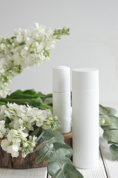 two white cosmetic jars, against flowers