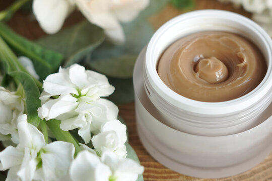 face cream, brown, against flowers