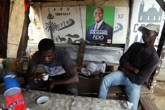 Men sit near a campaign poster of a presidential candidate Alassane Ouattara of the ruling RHDP coalition, in Abidjan