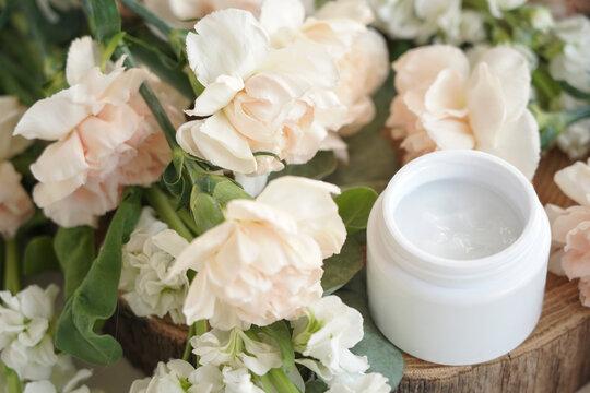 face cream, white, against flowers
