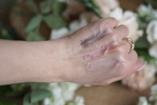 swatch on the hand of several options on a background of flowers