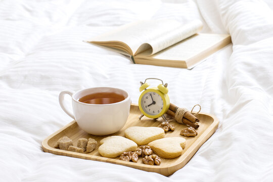 Good Morning Wishes Concept. Breakfast in bed. Beautiful composition on a wooden tray: tea with cookies, nuts. Book on the blanket is the theme of a lazy, comfortable time at home. 9:00 am.