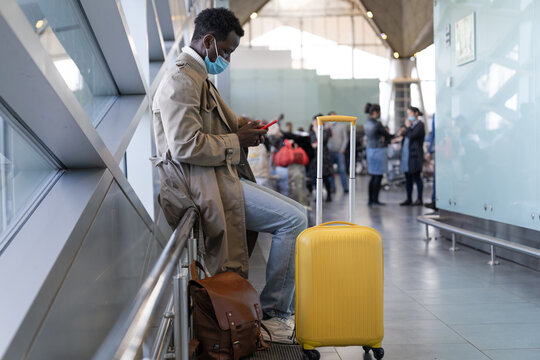 Afro-American traveler man in trench coat wear face protective mask, sitting in airport terminal or railway station, using mobile phone, waiting for flight and boarding. New normal, covid-19 pandemic.