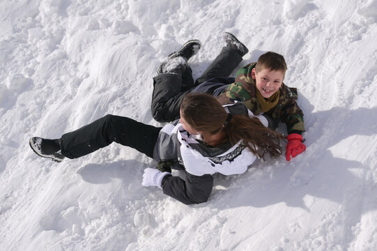 winter recreation leisure activity of kids boy and girl falling on white snow during winter christmas holiday vacation