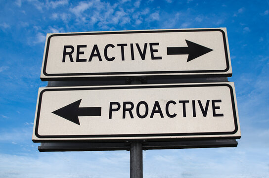 Reactive vs proactive. White two street signs with arrow on metal pole with word reactive and proactive. Directional road. Crossroads Road Sign, Two Arrow. Blue sky background.