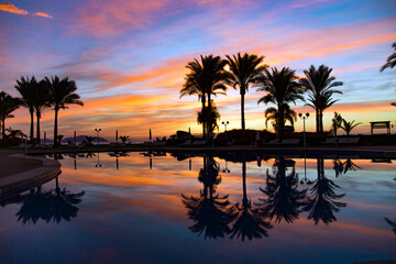 Beautiful bright sunrise reflected in the pool among palm trees over the Red Sea, Egypt