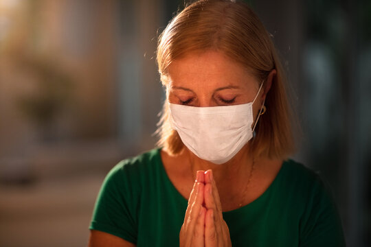 Woman in face mask praying for