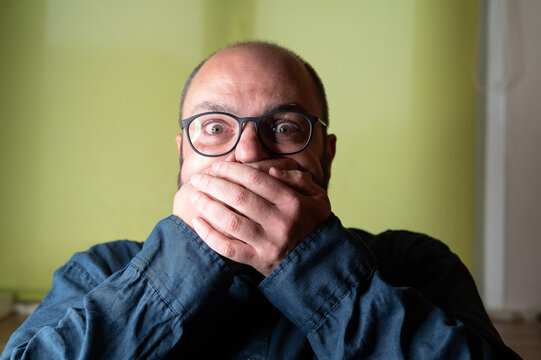 Man covers his mouth with both hands and looks scared into the camera