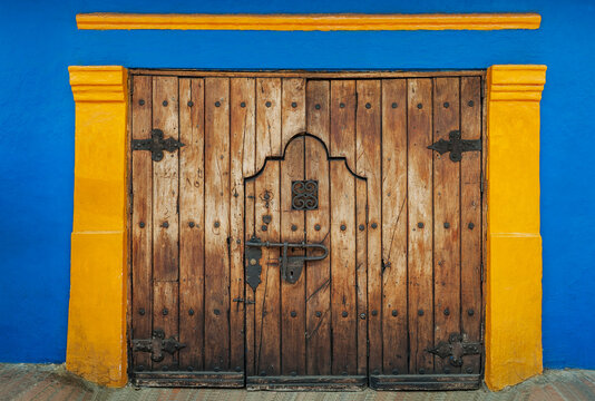 Bogota-Colombia-Closed wooden door with blue-yellow wall