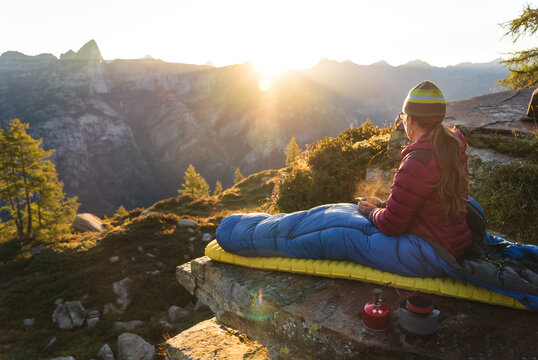 A woman enjoying breakfast from her bivouac on a beautiful morning in the mountains.