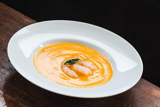 Butternut squash cream soup with shrimps plate.