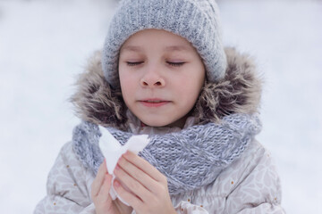 Girl with allergy symptom blowing nose. Teen girl using a tissue in a winter park.