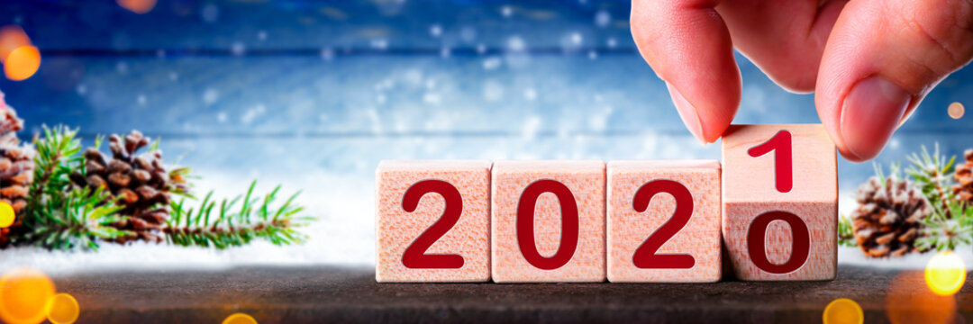 Hand Changing Date From 2020 To 2021 On Wooden Cube Calendar - Christmas And New Year's Concept