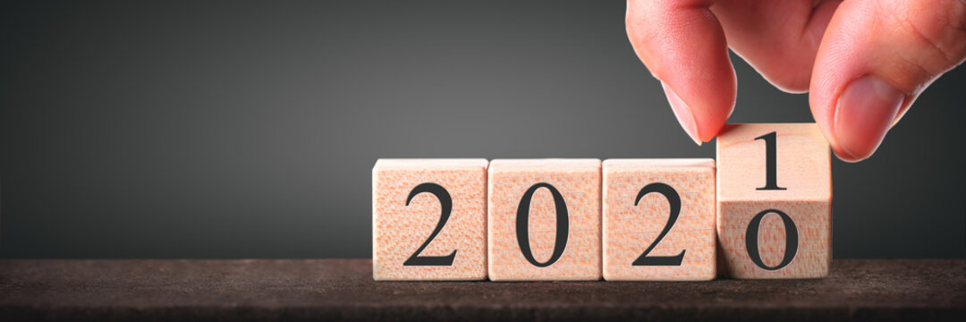 Hand Changing Date From 2020 To 2021 On Wooden Cube Calendar - New Year's Concept