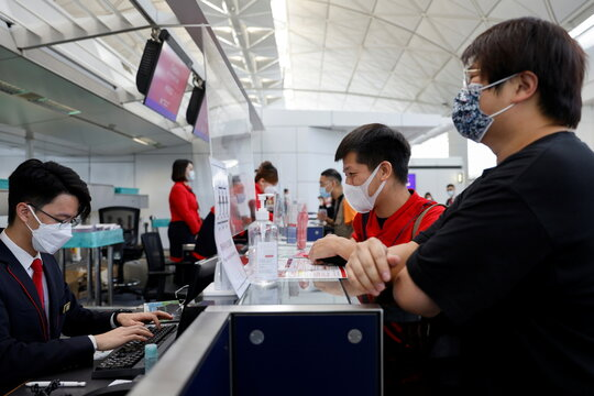 "A Hong Kong Airline's employee checks passengers' documents at the check-in desk before the Embrace ""Home"" Kong ""flight to nowhere"" experience, in Hong Kong"