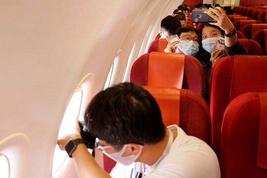 "Passengers take a selfie as they sit on board of the Hong Kong Airline's Embrace ""Home"" Kong ""flight to nowhere"" experience, in Hong Kong"