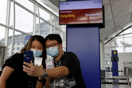 "Passengers take a selfie before boarding Hong Kong Airline's Embrace ""Home"" Kong ""flight to nowhere"" experience, in Hong Kong"