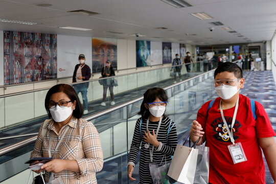 "Passengers wear face masks as they board Hong Kong Airline's Embrace ""Home"" Kong ""flight to nowhere"" experience, in Hong Kong"