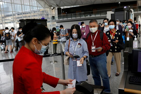 "A Hong Kong Airline's employee checks passengers' documents before boarding for Hong Kong Airline's Embrace ""Home"" Kong ""flight to nowhere"" experience, in Hong Kong"