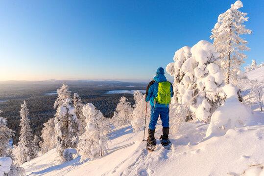 Hiker on snowshoes amongst frozen trees near Pyha in Lapland, Finland