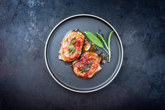 Modern Style traditionelle italienisches gebratenes  Saltimbocca alla Romana Schnitzel von Kalb Parma Schinken und Salbeiblätter angeboten als Draufsicht auf einem Nordic Design Teller