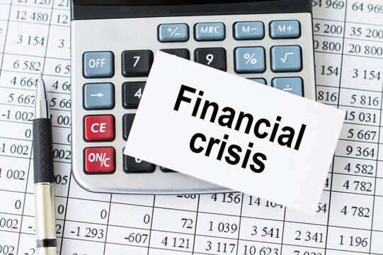 Financial crisis word written on a card lying on a calculator near a pen and financial reports