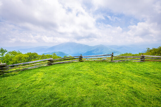 Devil's Knob Overlook with wooden fence and green grass field meadow at Wintergreen resort town village in Blue Ridge mountains in summer clouds mist fog