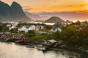 Beautiful colourful sunrise over Reine town and mountains in background during sunrise in Lofoten, Norway.