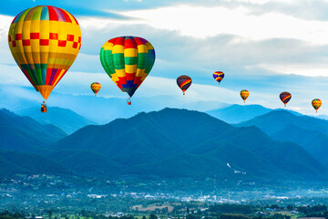 Colorful hot air balloons flying over mountain at  pai mae hong son Thailand.
