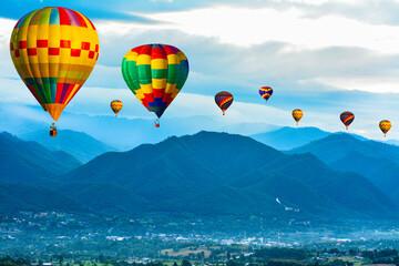 Colorful hot air balloons flying over mountain at  pai mae hong son Thailand.