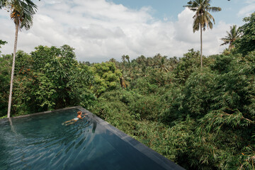 Young girl taking a bath and relaxing at infinity swimming pool surrounded with palm trees in tropical jungle