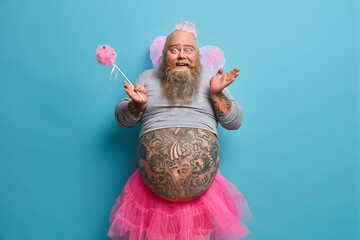 Funny happy bearded man has image of fairy holds magic wand poses with big tattooed belly over blue wall entertains children on party poses against blue background. Adult male dressed like princess