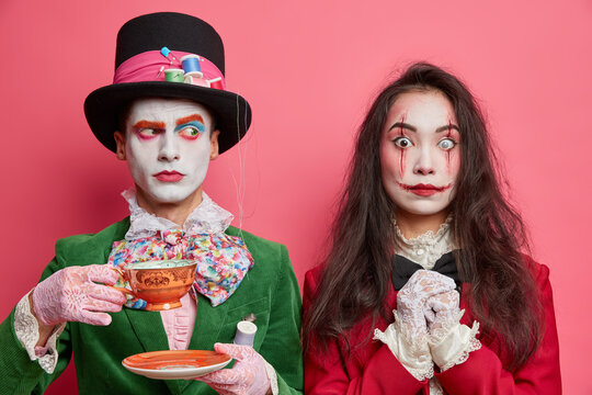 Serious man has image of hatter looks away and drinks tea dressed in green costume big bowtie and tall hat scary brunette woman zombie with bloody scars lens on eye isolated over pink background.