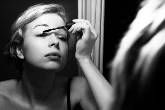 Woman getting ready for work doing morning makeup routine applying mascara in bathroom mirror at home. Beautiful caucasian girl applying eye make-up. Black and white image.
