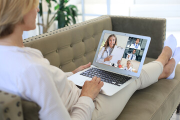 Fototapeta Middle aged woman making video call receive medical consultation on-line from diverse specialists. Patient in videoconferencing with doctors team on laptop. obraz