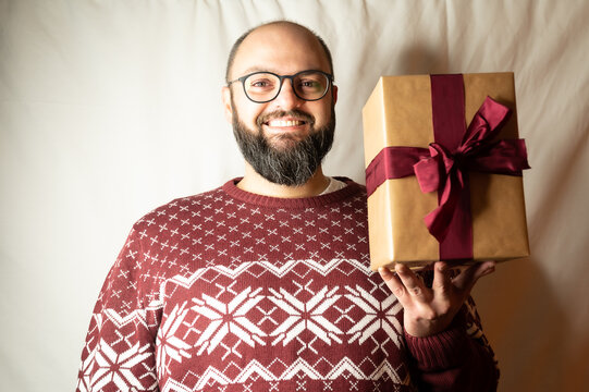 man is happy about a present and happily holds it in the camera