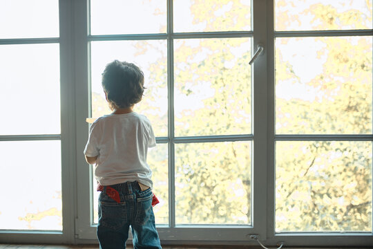 Indoor rear view of little boy with brown curly hair standing on windowsill by large window, looking outside, spending day at home alone, feeling bored. Childhood, family and domesticity concept